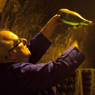 man looking at aged cava bottle